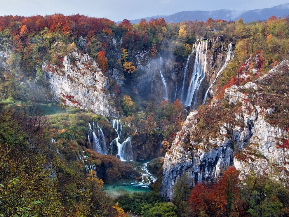 Dispersing fog and a moment of sunshine bring the falls and foliage of Croatia's Plitvice Lakes National Park into view on an early autumn morning