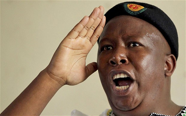 Julius Malema sings after addressing a group of civilian dress soldiers at the Lenasia Recreation Centre