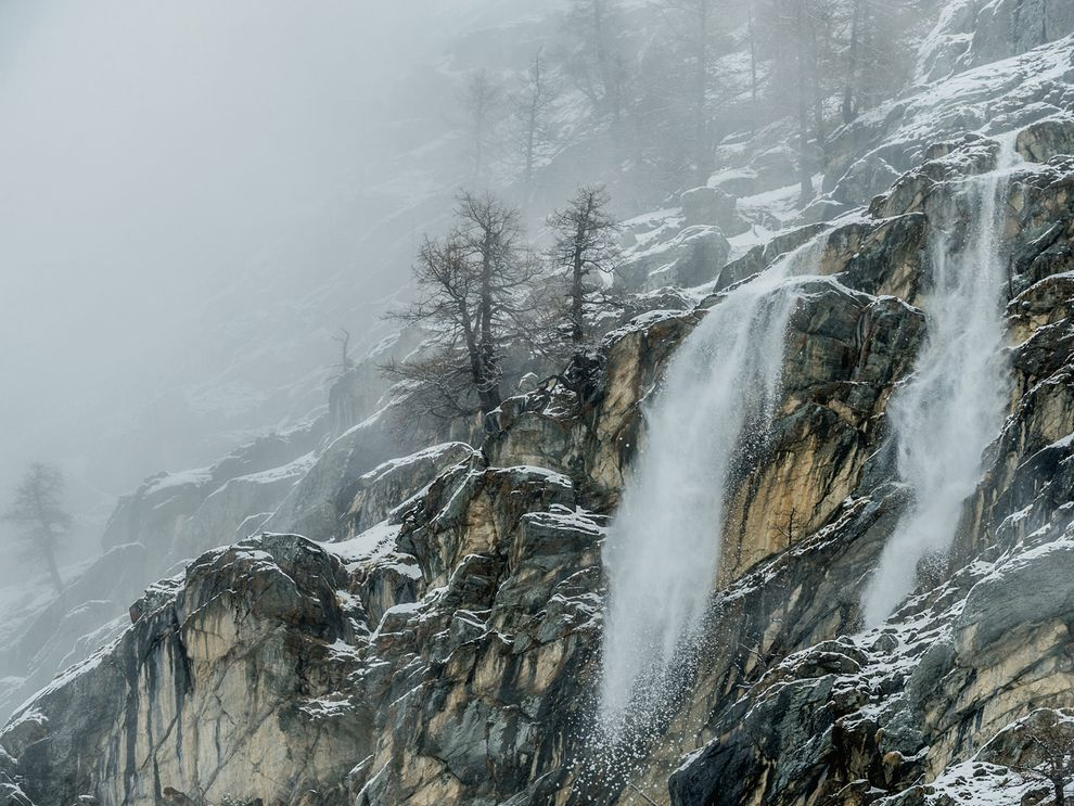 Late winter snow cascades down the rocky slopes of Valsavarenche valley in Italy's Gran Paradiso National Park