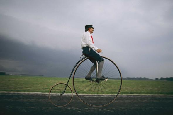A man in period dress in Indiana rides a Penny-Farthing, a two-wheeler popular in the late 1800s