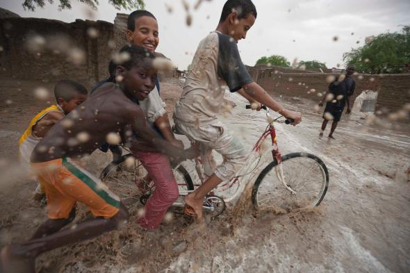 Mud and a bicycle add up to a playful combination in Timbuktu, Mali. Cycling is a global symbol of childhood