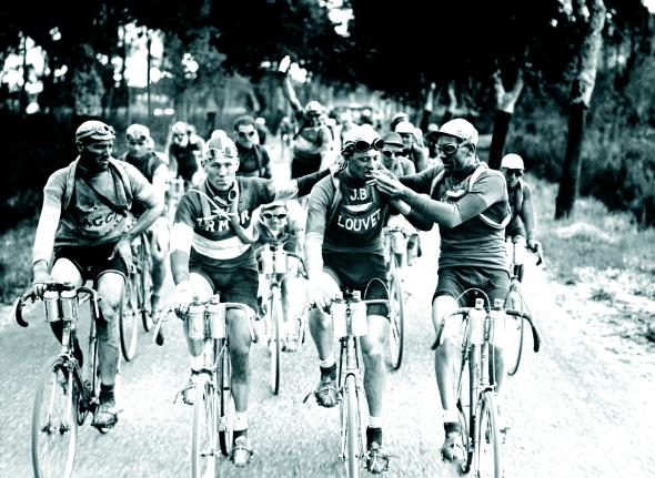 With spare tubes wrapped around their bodies, cyclists from a 1920s Tour de France light up along the way. In the early 1900s, a smoke was thought to provide a jumpstart to a race.
