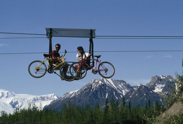 A couple ferries their mountain bikes above the Kennicott River in a hand tram in Wrangell-St. Elias National Park, Alaska. A footbridge now allows explorers on foot or wheels to venture across