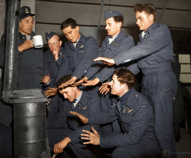 """The crew of Avro Lancaster """"C for Charlie"""" of No. 44 (Rhodesia) Squadron RAF, try to warm themselves in their Nissen hut quarters at Dunholme Lodge, Lincolnshire, England, after returning from a raid on Stuttgart, 2nd of March 1944. (Source - © IWM (CH 12379. Colorized by Paul Edwards)"""