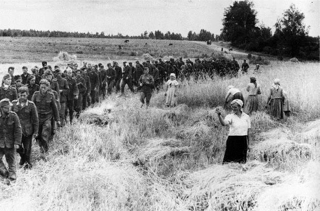 1944. German prisoners of war marching under the supervision of Soviet soldiers. The Soviet woman is showing a 'dulya' (the finger) with her hand