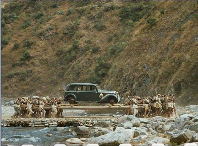 1950. Locals carrying a Rolls Royce in Nepal