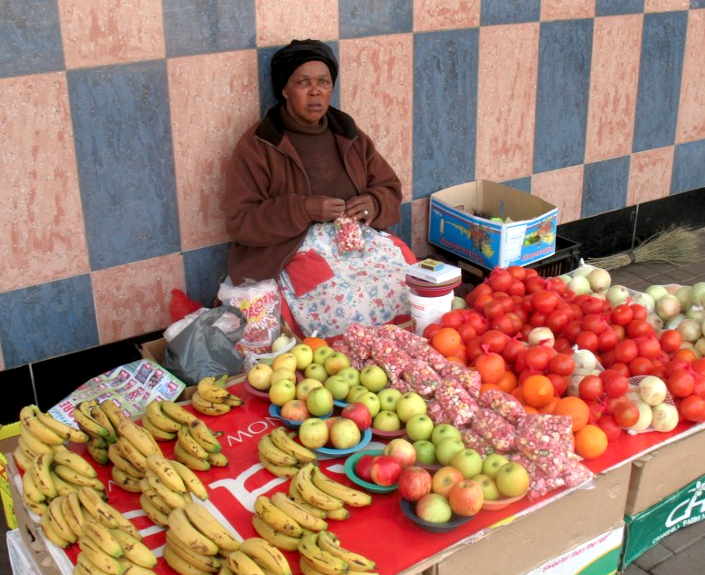 A street vendor in South Africa selling fresh produce to passersby
