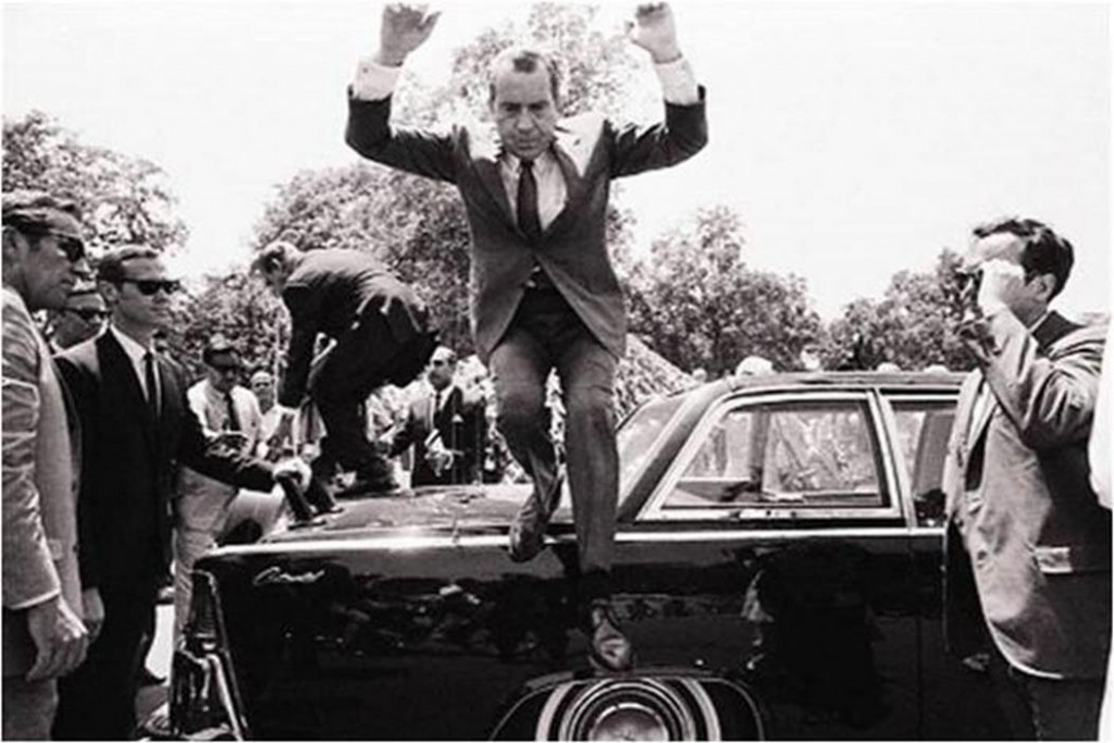US President Richard Nixon jumps down from the trunk of a limousine which carried him and Pakistani President Yahya Khan in a motorcade to Government House after Nixon's arrival in Lahore on August 1, 1969