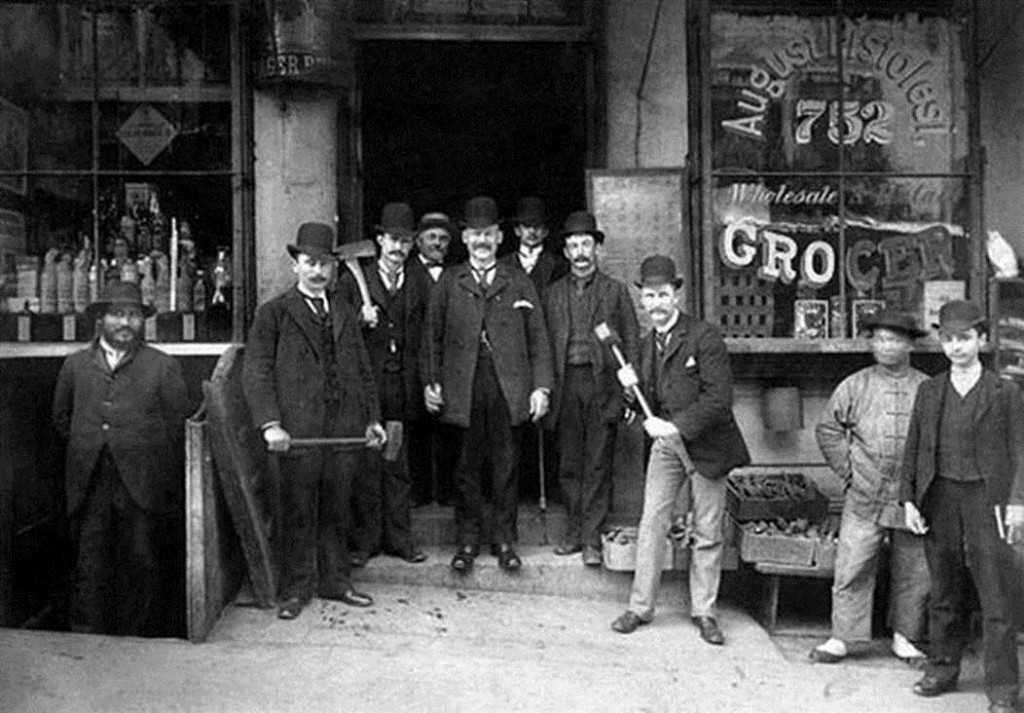 Chinatown Squad of the San Francisco Police Department posing with sledge hammers and axes in front of August Pistolesi's grocery store at 752 Washington Street, 1895