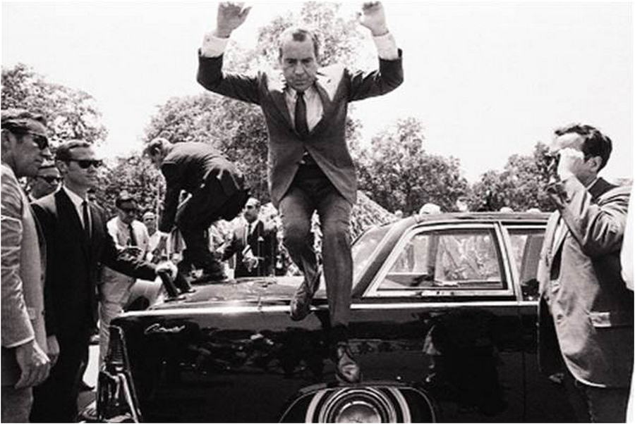 33 U.S. President Nixon jumps down from the trunk of a limousine carrying him & Pakistani President Yahya Khan in a motorcade to Government House in Lahore on August 1, 1969