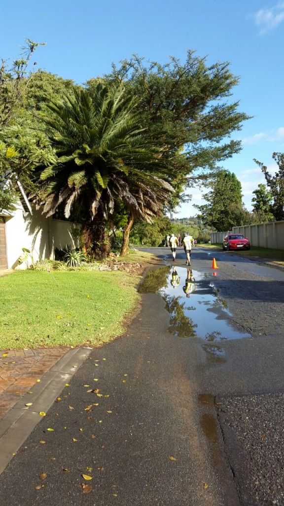 The reflections of runners in the rapidly receding pools in the road