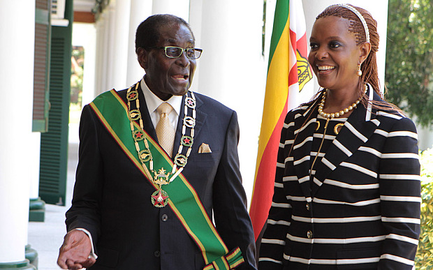 Zimbabwe President Robert Mugabe stands with his wife Grace, as they pose for a photo at State House in Harare, Tuesday, Oct, 28, 2014. Muagbe officially opened the first session of the 8th parliament of Zimbabwe in Harare where he called on the government to deal with the ever rising housing backlog across the country. (AP Photo/Tsvangirayi Mukwazhi)