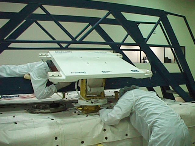 SHUCS antenna being fitted on top of the Spacehab module. This whole module is then fitted into the cargo bay of the space shuttle