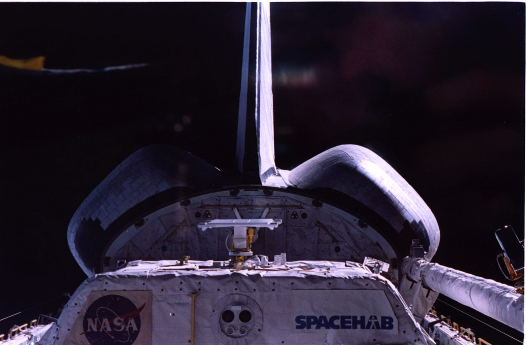 SHUCS finally in space - The antenna is in a roughly horizontal attitude on top of a positioner, on top of a Spacehab module at the back of the Shuttle cargo bay.