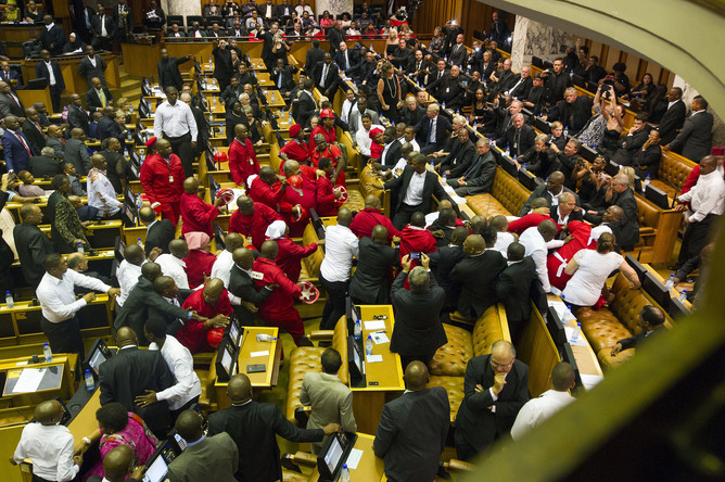 Members of Julius Malema's Economic Freedom Fighters (EFF) (in red) clash with security officials after being ordered out of the chamber during President Jacob Zuma's State of the Nation address in Cape Town, February 12, 2015. The opening of South Africa's parliament descended into chaos on Thursday as security officers fought with far-left Economic Freedom Fighters (EFF) lawmakers after they disrupted President Jacob Zuma's speech.  REUTERS/Rodger Bosch/Pool (SOUTH AFRICA - Tags: POLITICS CIVIL UNREST CRIME LAW TPX IMAGES OF THE DAY) - RTR4PD5Z