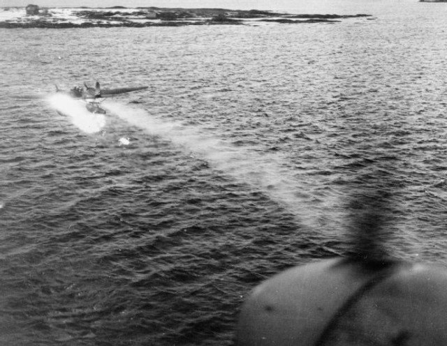 "A German Heinkel He 115 on fire and trailing smoke, photographed by the observer of De Havilland Mosquito ""P"" of No. 333 (Norwegian) Squadron RAF based at Leuchars, Fife (UK), which intercepted the seaplane 60 m above the sea off Bremanger, Norway, while conducting a shipping reconnaissance. The Mosquito closed to within 200 m to finish off the Heinkel with cannon fire, which crashed into the sea shortly afterwards."