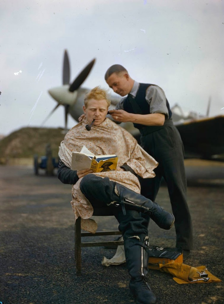 An RAF pilot getting a haircut while reading a book between missions