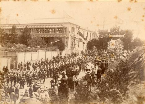 Scenes during the visit of Lord Loch, 27 January, 1890. Procession nearing the top of White's Road. Men of the P.A.G. Regiment in procession. Decorative archway at the top of the road. Grand Hotel with spectators lining the balconies.
