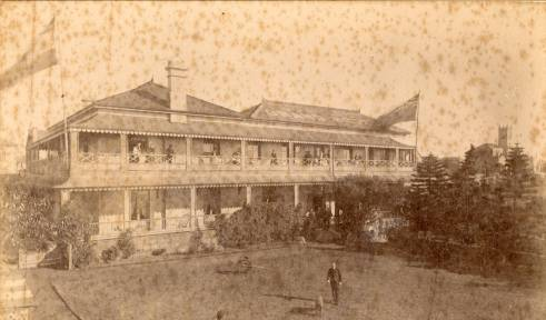 The rear of Bunton's Grand Hotel taken from the hotel grounds with guests standing on the balcony.