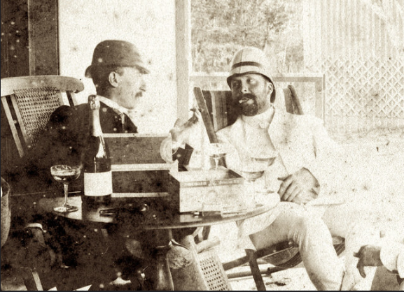 Howard Mapplebeck in 1886 in his Emerald Hill home with an unknown person. Typically he is dressed in white with a pith helmet