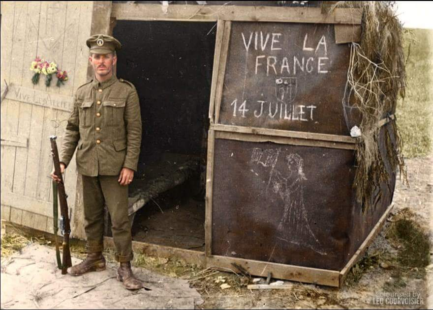 A South African sentry stands guard at a crossroads in front of a hut decorated in honour of the French Bastille Day, in the Vaux-sur-Somme, area, 14 July 1916.