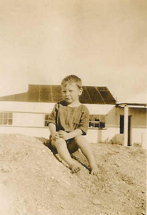 Bryce McCleland (6 to 8 yrs old) playing on a pile of sand next to The Hut Tearoom at Schoenmaker's Kop