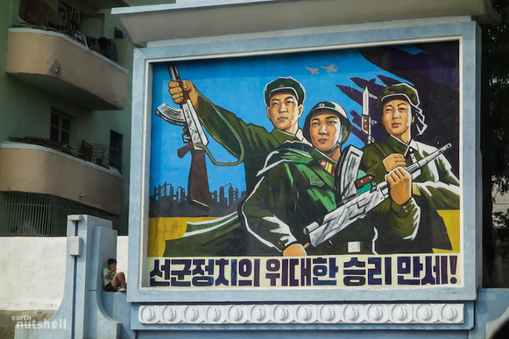 a-young-boy-sits-innocently-within-a-giant-militaristic-propaganda-mural-in-the-city-of-haeju