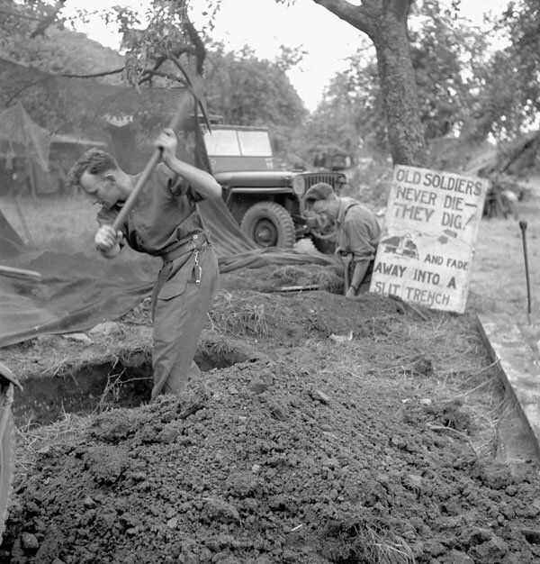 a-signalman-and-an-officer-of-the-royal-canadian-corps-of-signals-digging-a-slit-trench-ifs-france-july-1944