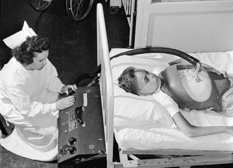 A boy suffering from polio being treated with a type of 'iron lung' in hospital. A nurse operates the equipment at the end of the bed which controls the flow of air pressure