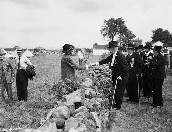 Confederate and Union soldiers shake hands across the wall at the 1938 reunion for the Veterans of the Battle of Gettysburg