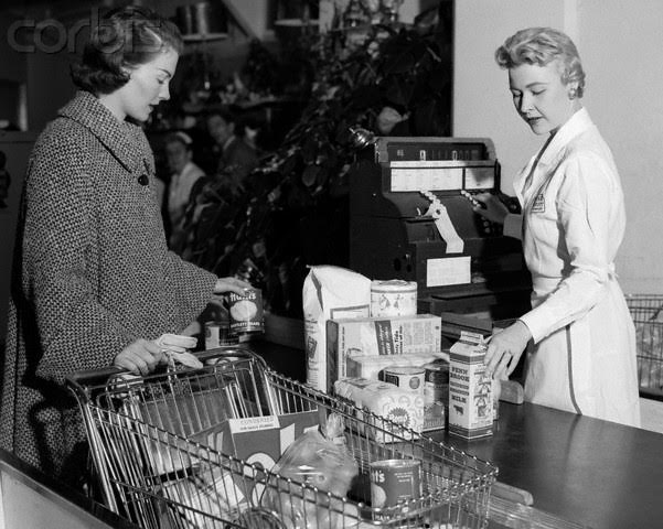 28 Jan 1954 --- 1950s Woman At Grocery Store Checkout Counter Handing Items Over to Cashier --- Image by © H. Armstrong Roberts/ClassicStock/Corbis