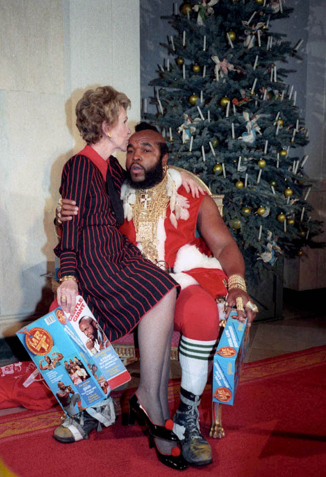 Nancy Reagan sits on the lap of Mr. T, dressed as Santa, 1983