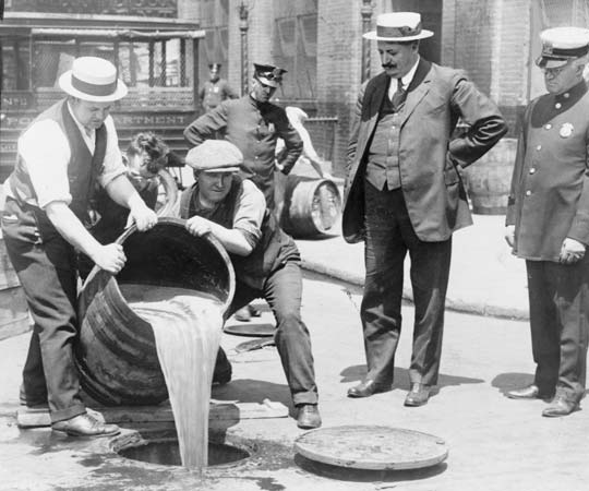 New York City Deputy Police Commissioner John A. Leach (right) watching agents pour booze down the drain