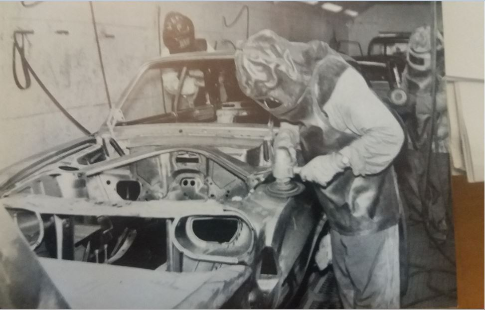 A Ford workman smoothing down the seven pounds of solder used on a motor vehicle