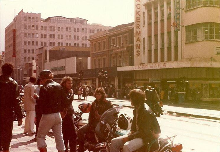 Bikers relaxing in Main Street (looking North) probably looking for kak while giving the local yokels something to gawk at