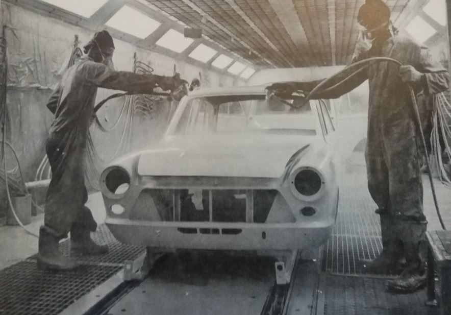 Ford sprayers manually spraying two gallons of enamel paint onto the shell of a car