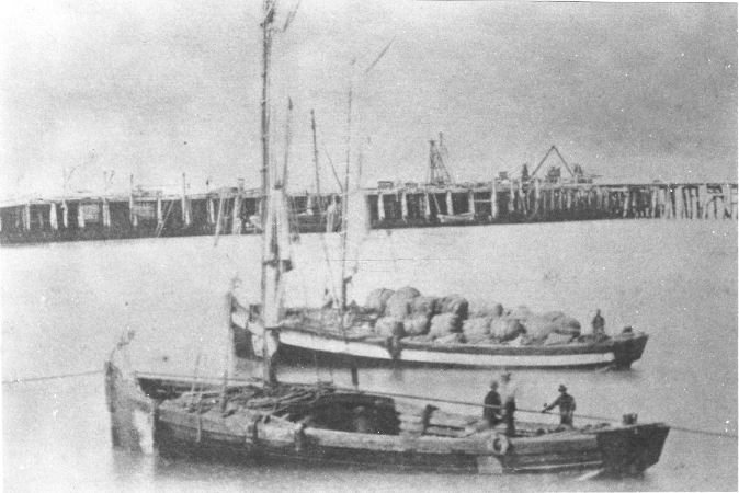 Harbour in 1870 with lighters and surfboats in the foreground and the original breakwater in the background