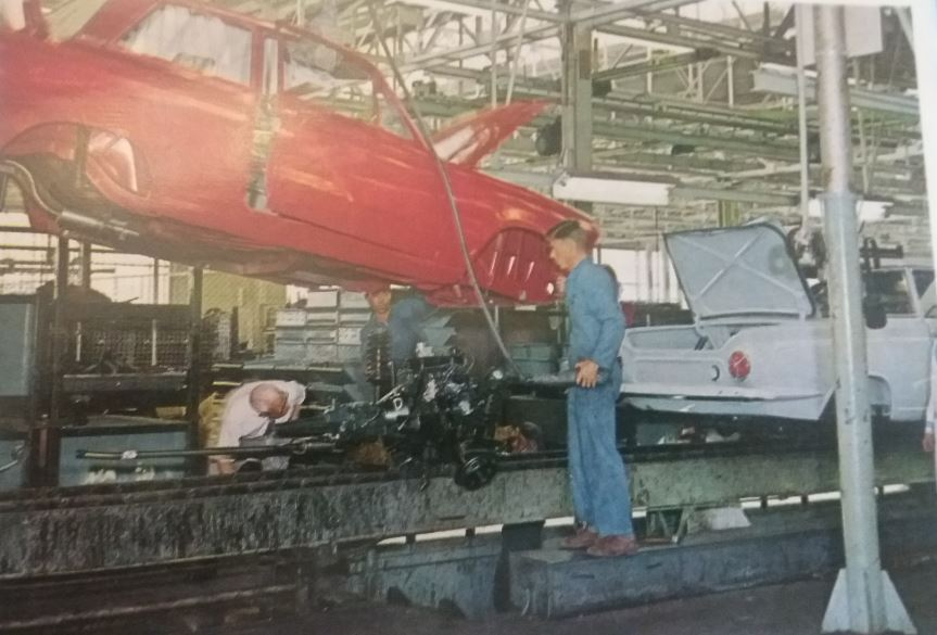 On the Ford assembly line, a car body is being lowered onto the vehicles chassis and engine