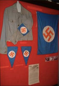 IHere is a rare and very unique display of South Africa's very own Nazi Party's shirts, flags and bunting.  Of interest, is the use of Orange, Blue and White in the Nazi swastika configuration – this was intentionally done to reflect the national colours of the South African flag at the time, the 'Oranje-blanje-blou'.